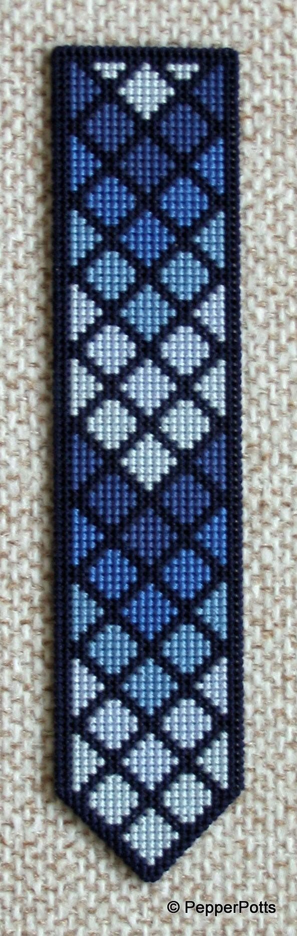Worked on 14ct plastic canvas in a cross stitch, using various shades of blue stranded cotton leftovers. The diamonds were worked first, then the contrasting lines filled in in a very dark navy blue stranded cotton. It is backed with thin craft foam using a double sided adhesive film.