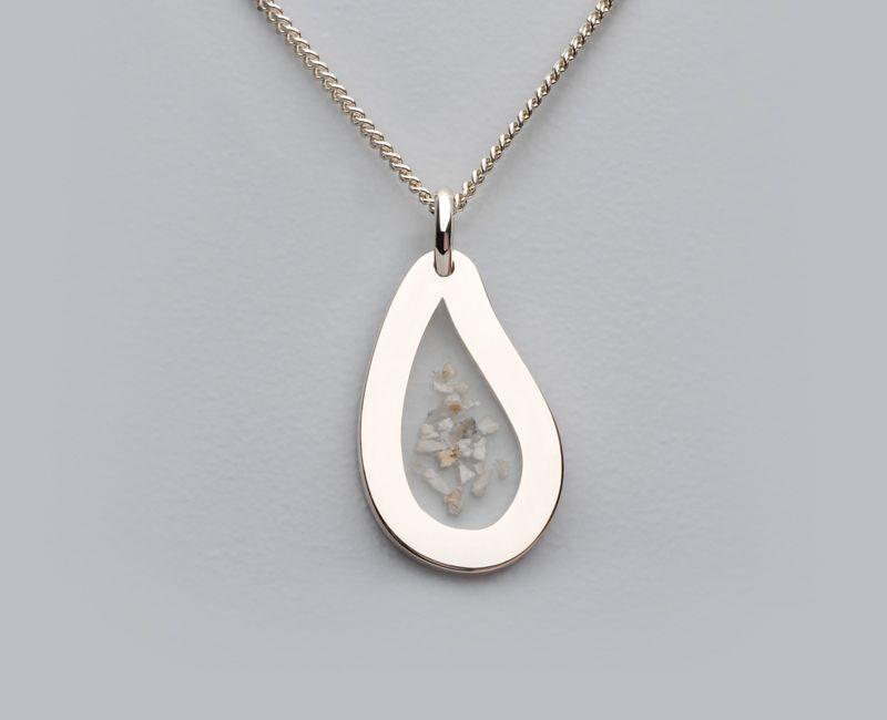 Een zilveren of witgouden ashanger in een druppelvorm. Het as is zichtbaar verwerkt in transparant clear ceramic.