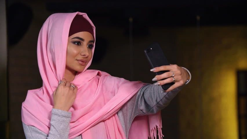 Young beautiful woman in hijab doing selfie on mobile phone camera. Muslim woman and modern technol
