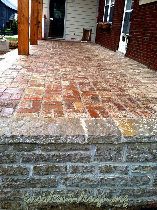 the raised limestone porch with reclaimed brick patio