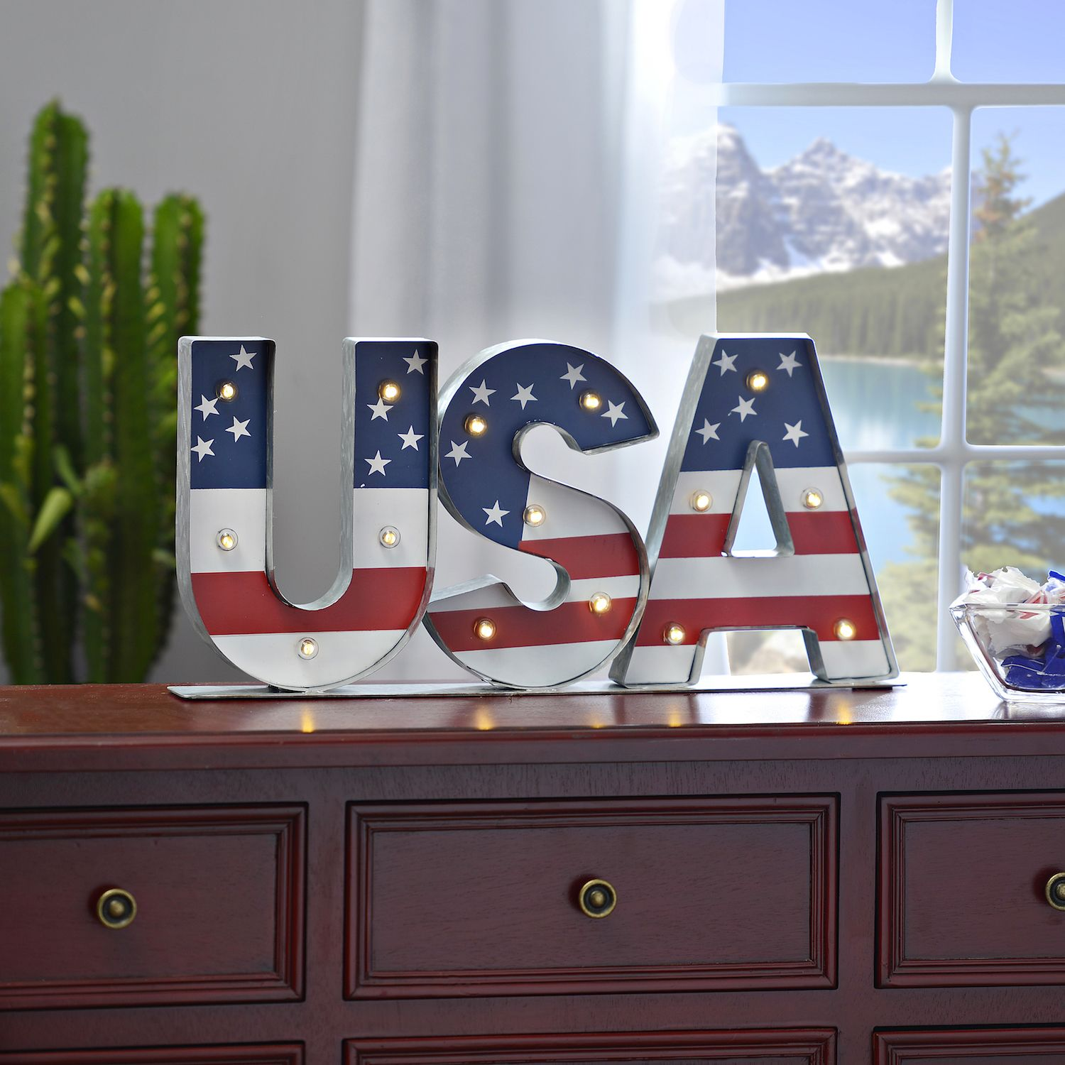 Get ready for this 4th of July season by showing off your glowing patriotism. This USA table top sign is made of metal and features pre-lit LED bulbs across red, white, and blue flag details. It's the perfect patriotic touch for your entryway or bookshelf this summer!