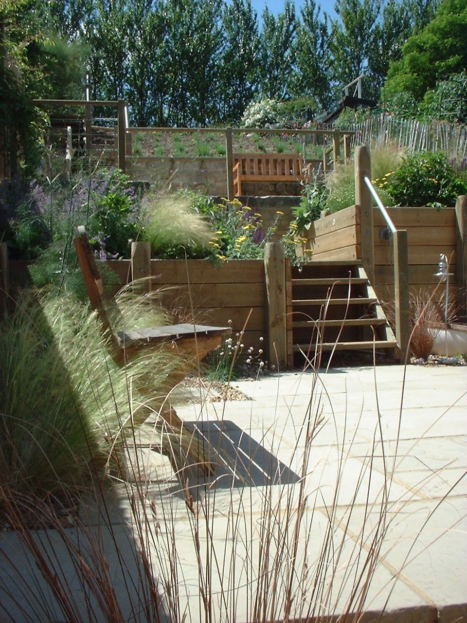 Terrace garden: patio leading to first tier, gradual slope with ...