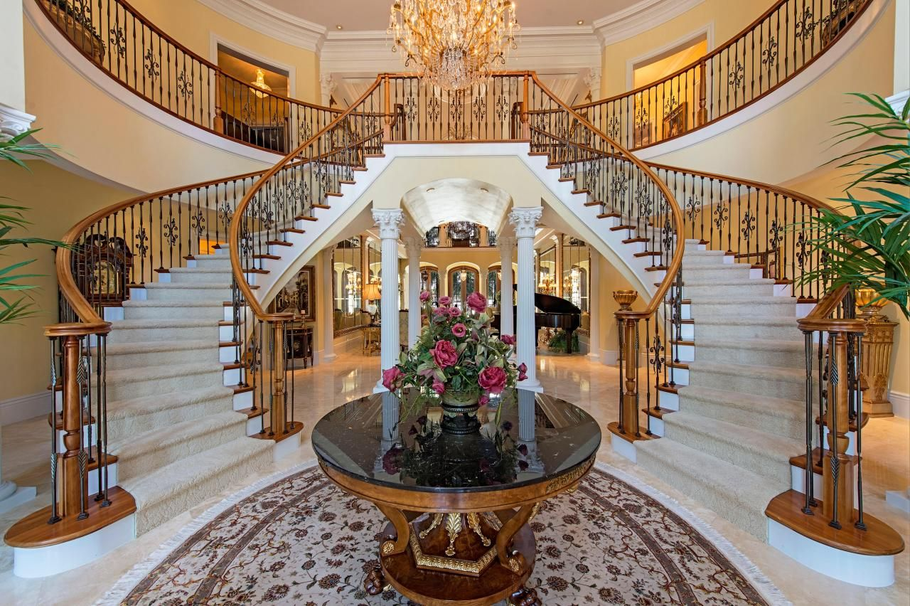 Mansion Foyer Chandelier : Beautiful twin sweeping staircases make for a grand