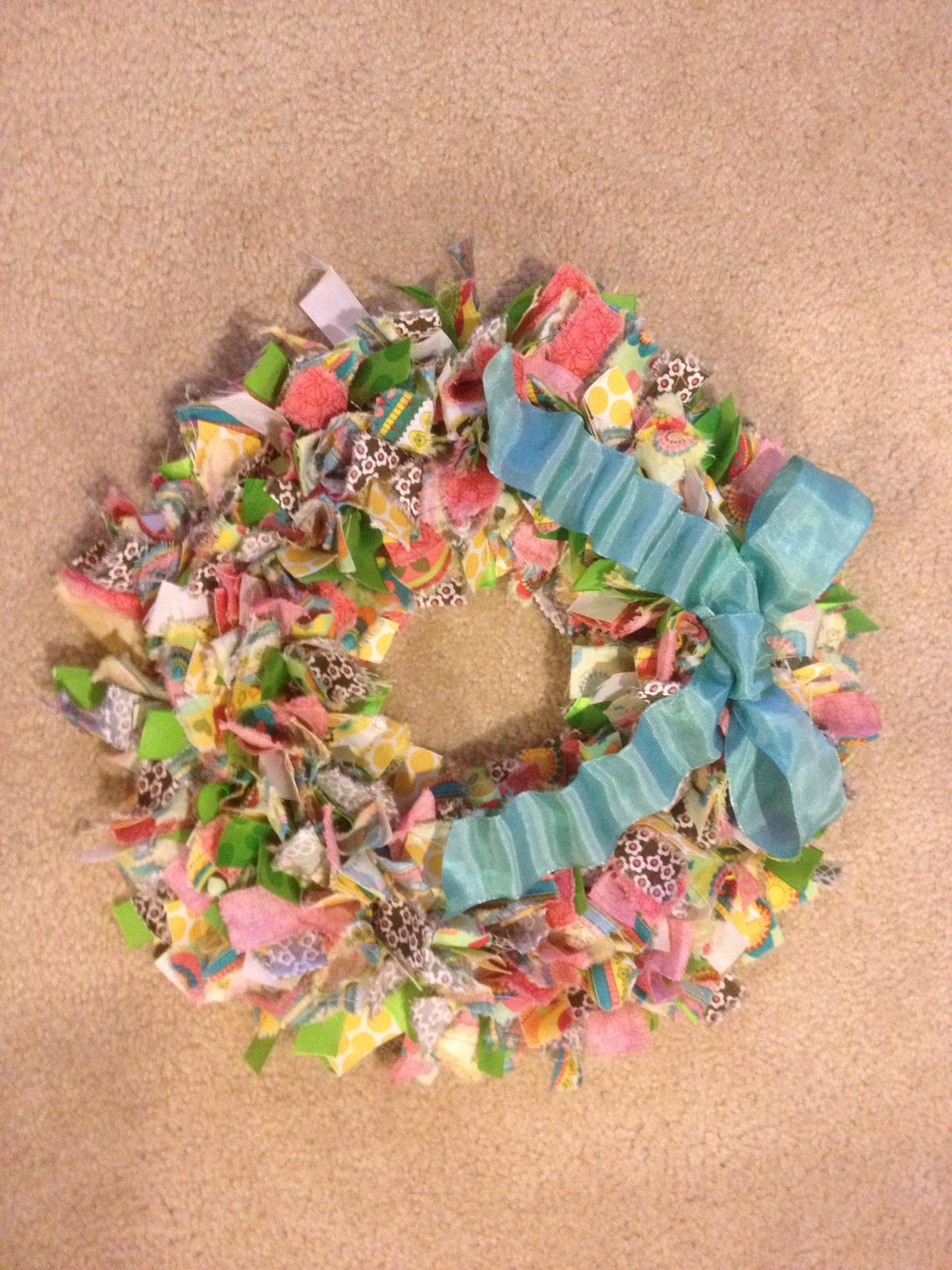 Spring/Summer Rag Tie Wreath I made for a friend. I used a quarter bundle from Joann's and two different rolls of coordinating ribbon cut the same length as the rag-ties (1-1/2 inches by 7 inches). Then I found an accent colored ribbon for the bow.  It's super easy and fun to make. I liked ripping apart the fabric. It's a good way to release stress! :)