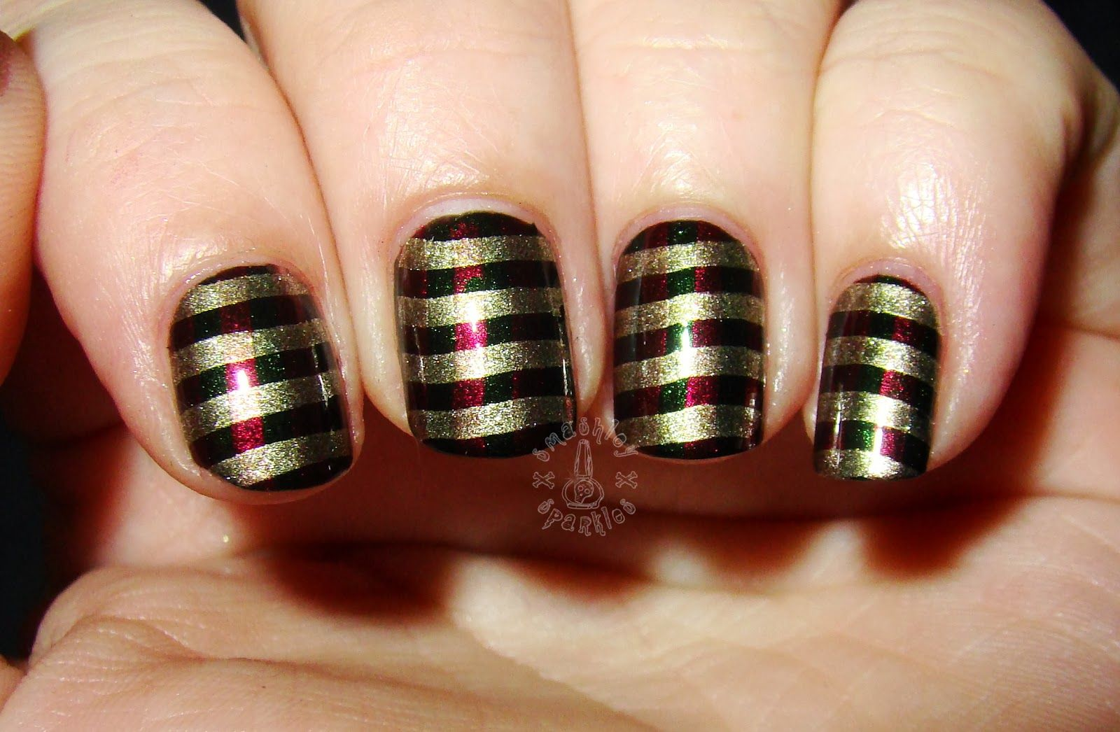 A Christmas nail design in red,green and gold stripes