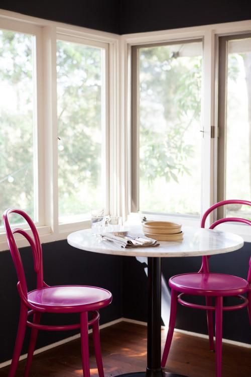 Hot pink bentwood chairs, marble top table, black walls
