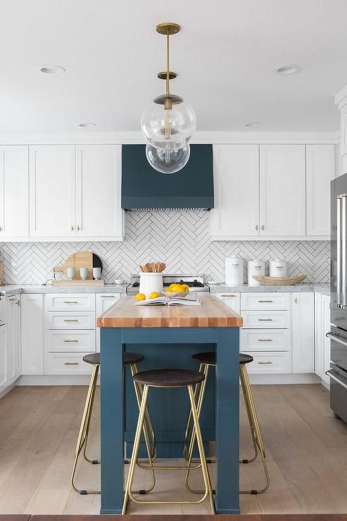 A butcher block countertop accents a blue kitchen island lit by ...
