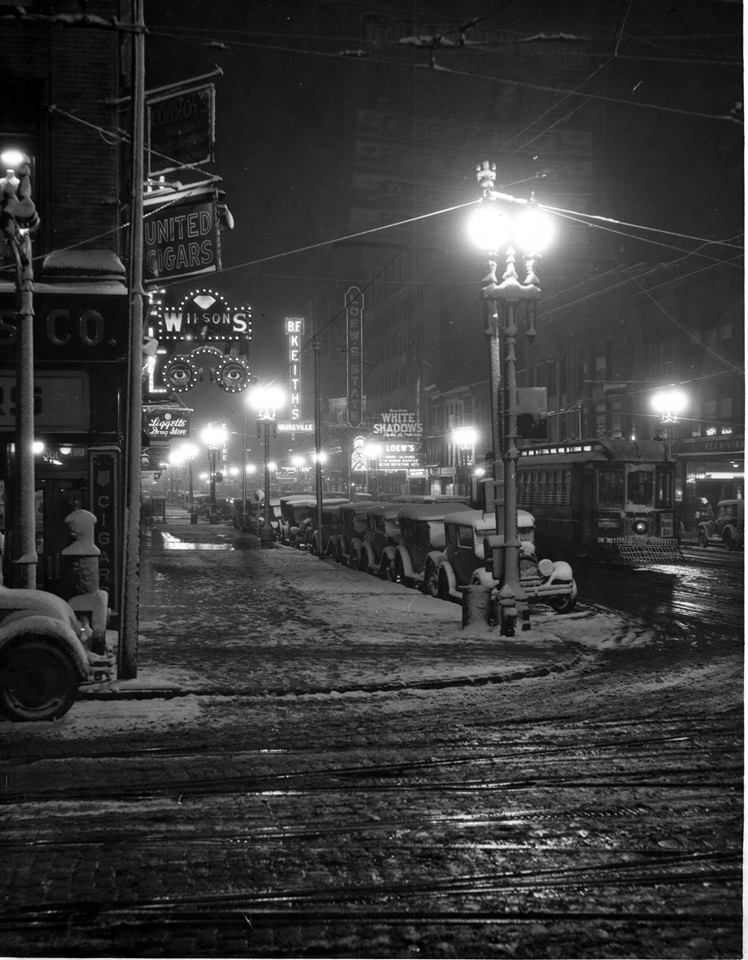 "Looking down Salina Street we see the ""Butternut"" trolley car coming up the street. Lighted signs include ""Wilson's"", ""B.F. Keith's Vaudeville"", ""Loew's State"", ""Liggett's Drug Store"" and ""Empire"". Automobiles are parked along the street and no pedestrians are visible. Written on back of print: ""Downtown - looking south on Salina Street from Hunter-Tuppen Store, taken after the first snow fall of the Season."" ca.1928  -""Schuelke Collection, courtesy of the Liverpool Public Library."""