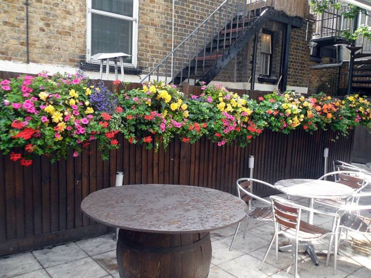 Jardines modernos vallas de madera con macetas colgantes for Macetas para jardin