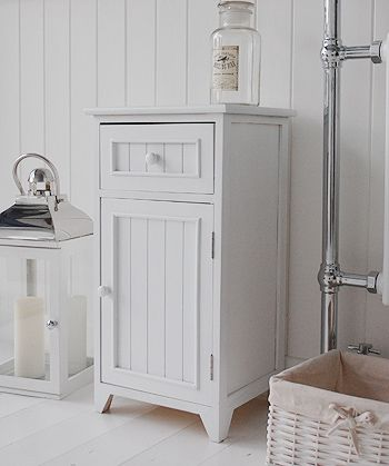 . A crisp white freestanding bathroom storage furniture  A narrow