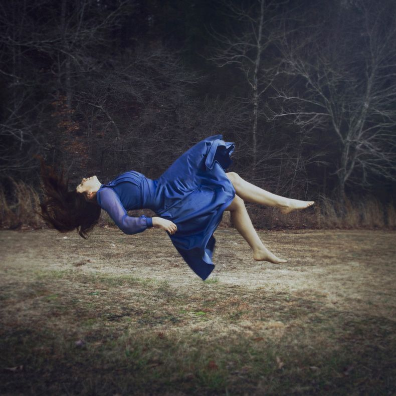 Levitation in the woods in a blue dress. Fine Art Photography by Judith Hill Photography.