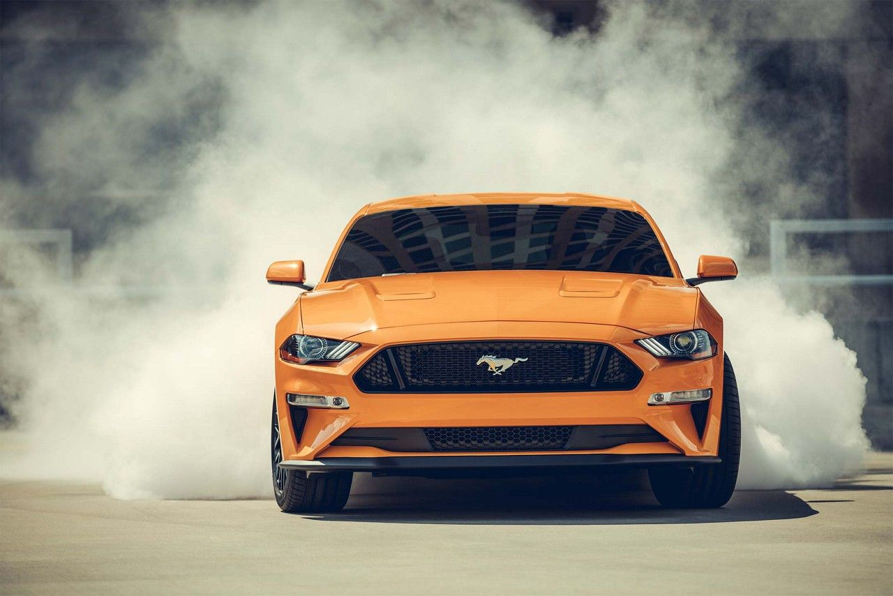 Mustang Gt In Orange Fury Tri Coat Doing A Burnout With Smoke Surrounding The Rear Tires