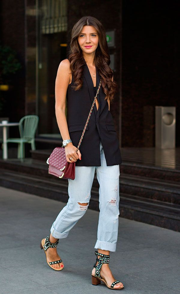 Street style look com colete preto, calça jeans e salto blocado.