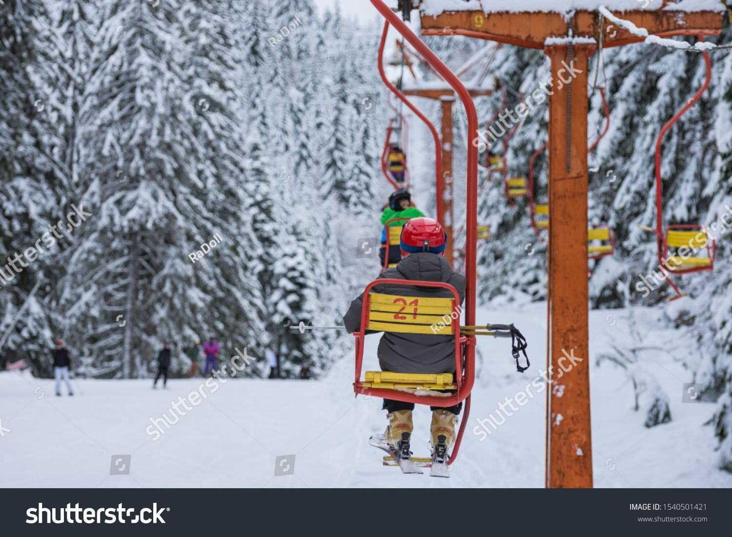 Skiers are sitting at old fashioned one chair ski lift