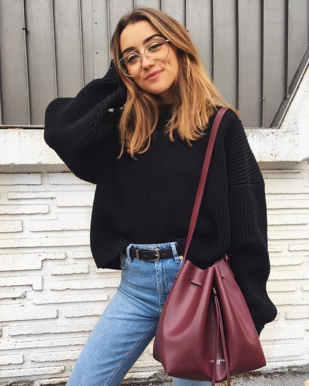 Oversized black sweater, high waisted jeans and burgundy handbag.