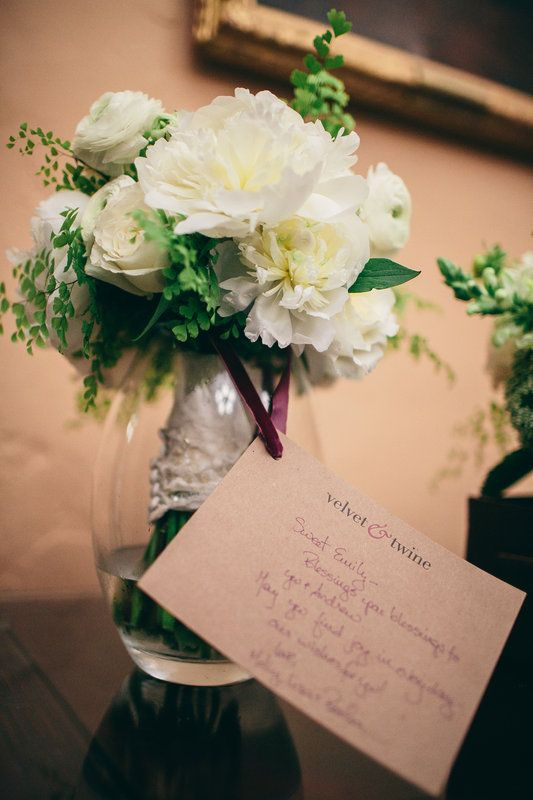 the brides bouquet is delivered to her dressing room the bouquet of white garden roses white peonies white ranunculus and maiden hair fern is tied with