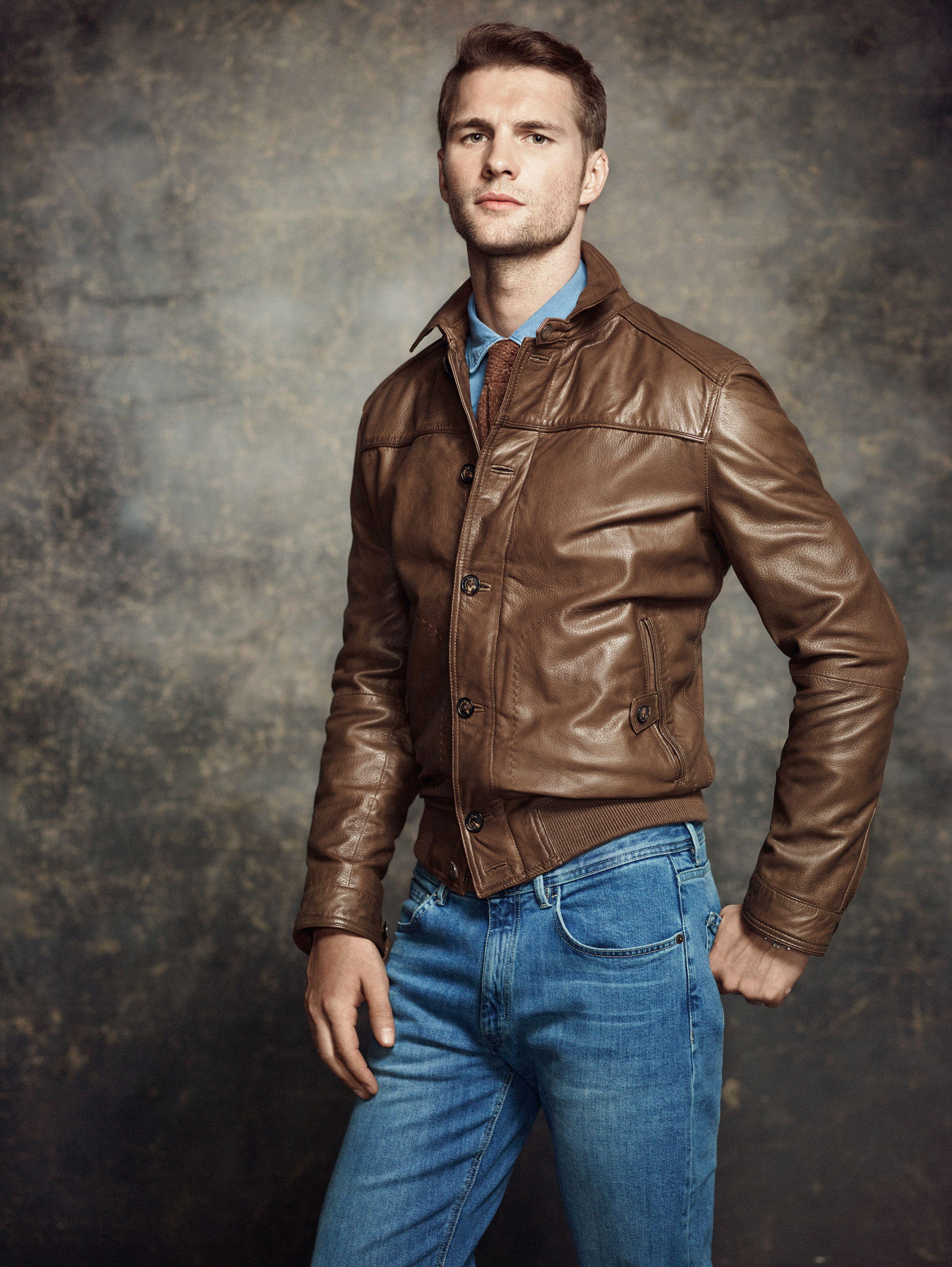 Brown leather jacket, denim shirt, brown knit tie, blue