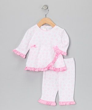 Featuring a unique wrap silhouette and loads of frilly ruffles at the cuffs and hemline, this sweet set is ready to shine. It's made from soft cotton, so it's as comfy as it is cute.