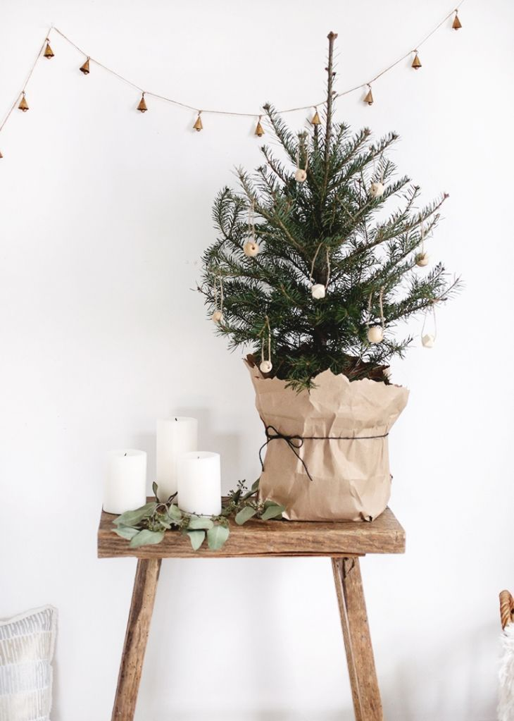 Photo of A natural indoor winter display with candles, a wooden stool and a small fir tre…