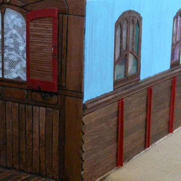 """Angle arrière de la roulotte ( en cours). Bâtons de glace pour la partie basse couleur chêne, """"touilletes"""" à café en bois repeintes en rouge, lamelles de sets de table en faux bambou repeintes en bleu ciel. Des volets sont à venir aux fenêtres."""