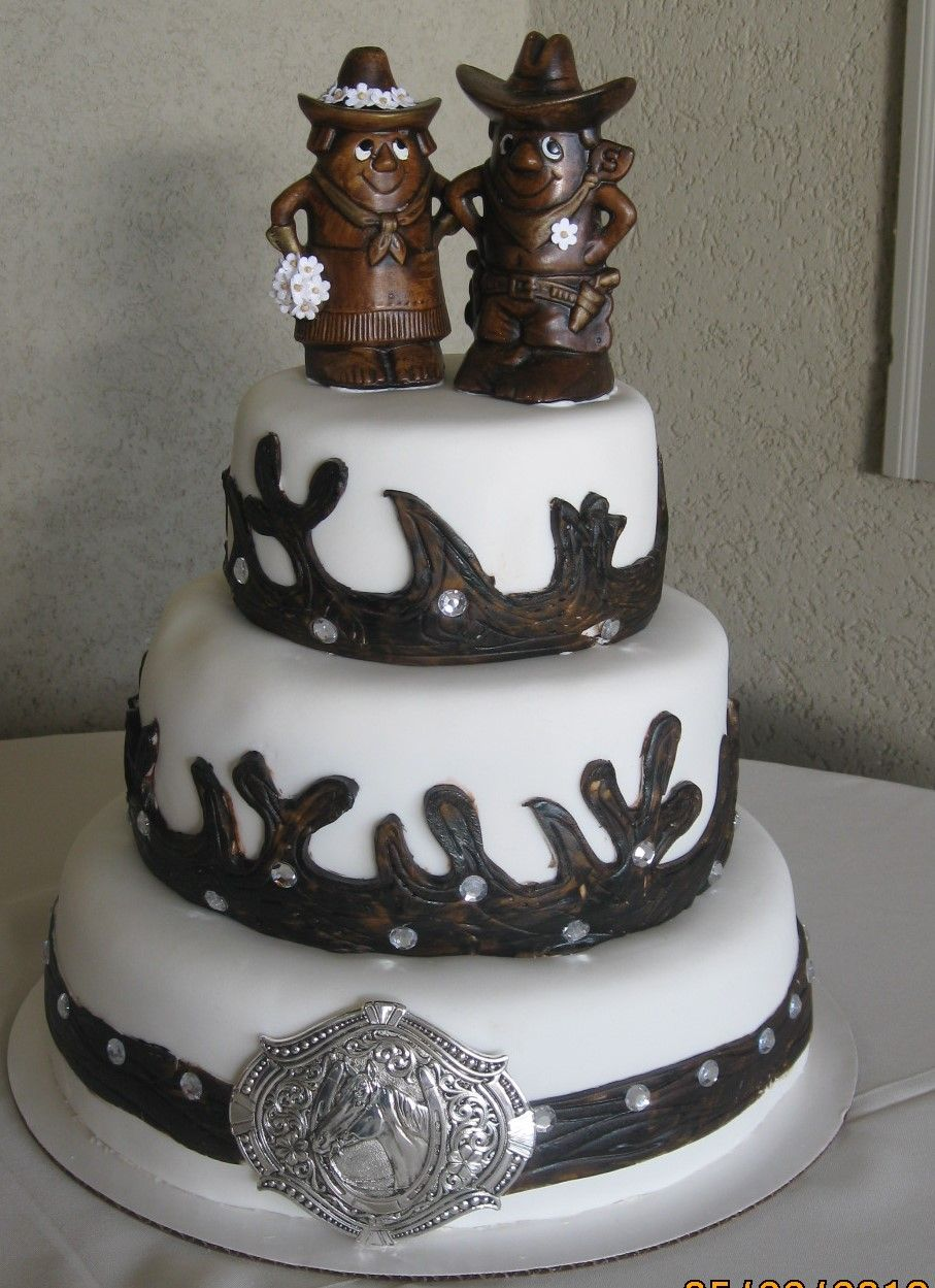 Wedding cake for a western wedding. The toppers are salt and pepper shakers obtained at an estate sale. The belt buckle is real.
