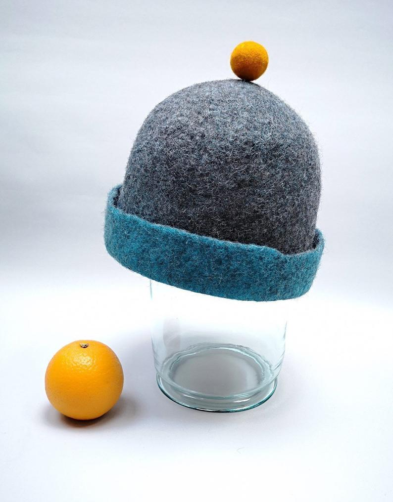 Rough edged graphite grey or teal blue bobble close fitting beanie hat natural wool saunaoutdoors charcoal gray cloche with a orange bobble