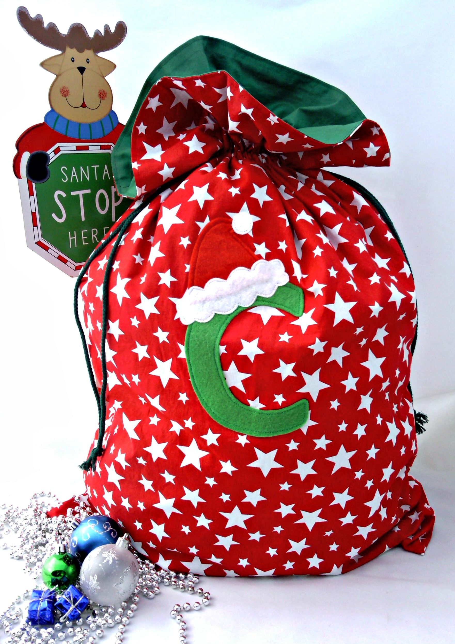 These gorgeous PERSONALISED Christmas Sacks are sure to bring squeals of delight from your child this Christmas. Made from Cotton fabric, fully lined for extra strength and durability it is sure to hold those special gifts. It features a double drawstring closure, felt initial and co-ordinating santa hat. A perfect gift that will be treasured for years to come. 50cm wide x 60cm tall (up to drawstring closure)