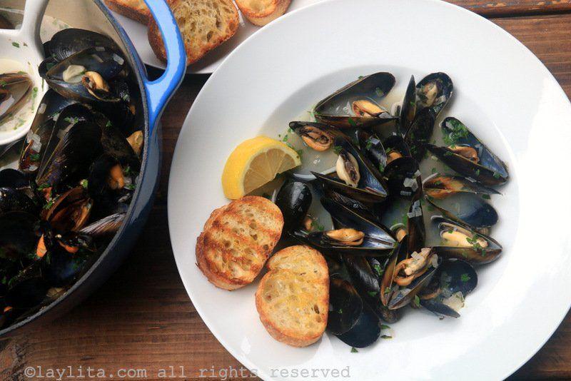 Receta para preparar mejillones al vino blanco, moules marinière o mejillones a la marinera. Los mejillones se cocinan al vapor en una salsa de vino blanco con mantequilla, ajo, chalotes, perejil, tomillo.