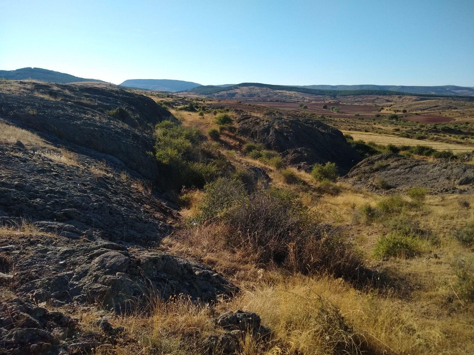 En el paisaje de llanuras manchegas, amarillo por las hierbas secas, destacan lenguas de piedra oscura que no se parece a nada de lo que la rodea. Estamos ante las Andesitas volcánicas