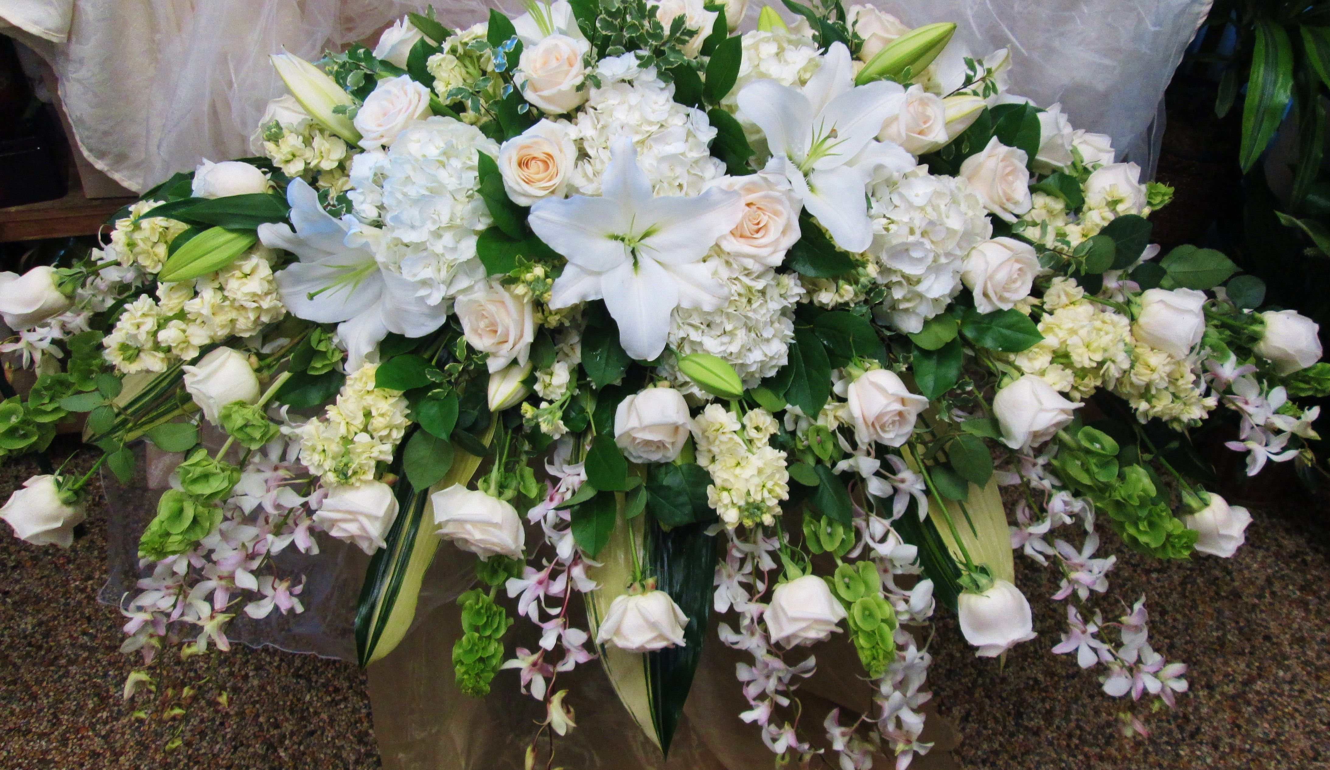 White Casket Spray Lilies Bells Of Ireland Yellow Stock Dendrobium Orchids White Roses And Ve Funeral Flowers Casket Flowers Funeral Flower Arrangements