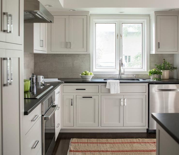 Superior Chic Kitchen Features Extra Light Gray Cabinets Paired With Black Quartz  Countertops And A Linear Gray Tile Backsplash.