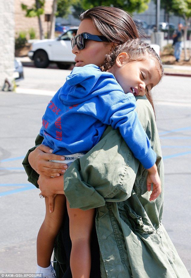 Not too heavy: Kim held onto North with both hands as the child slept...