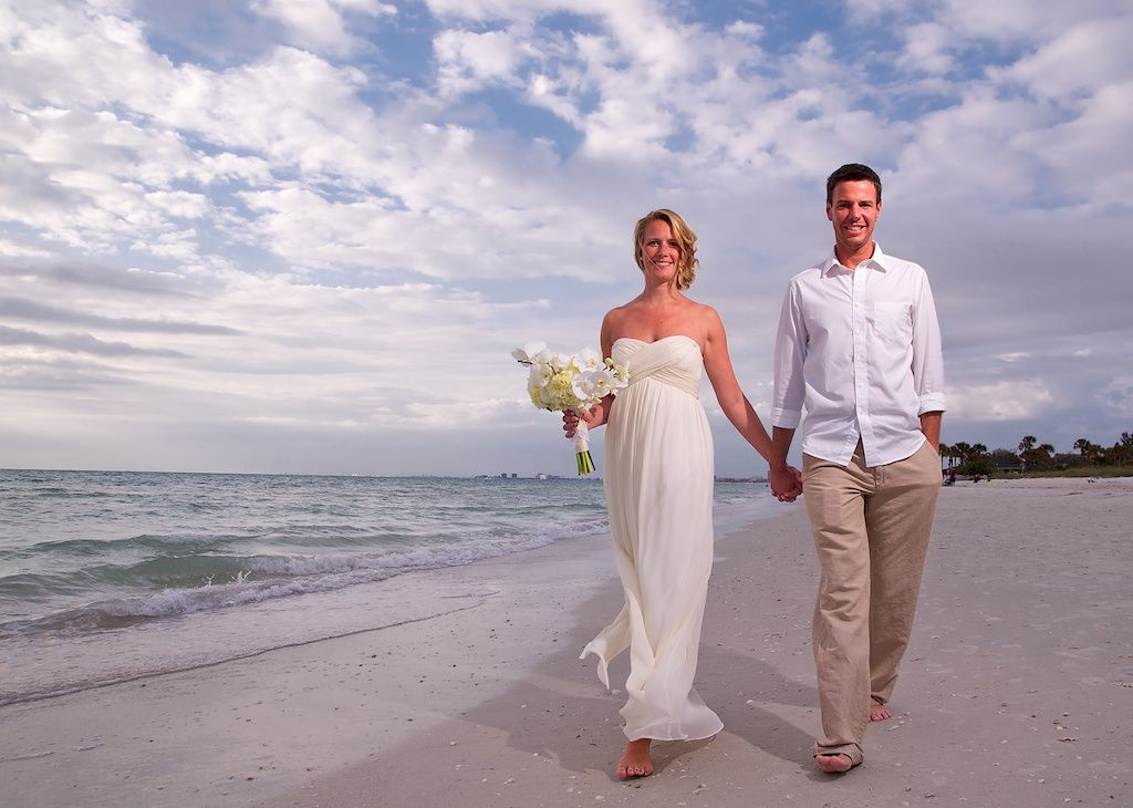 A Sweet Bride And Groom Walking Along The Shore After