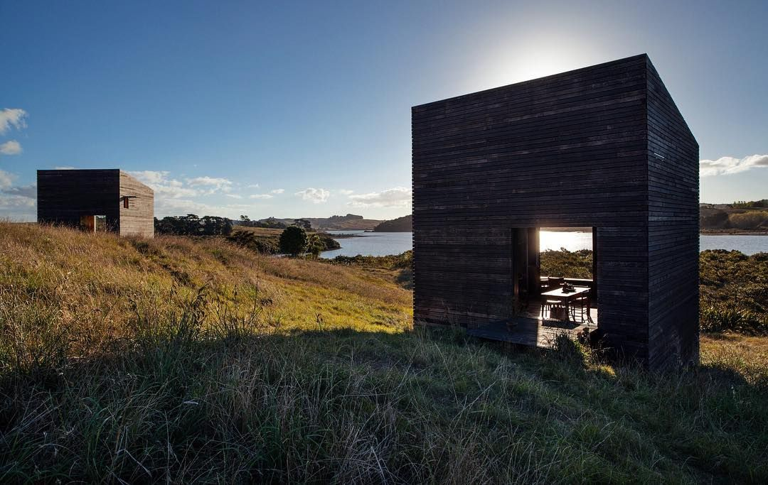 Before building on the North Island of New Zealand, two friends spent years replanting the site. The 290-square-foot structures Cheshire Architects designed for them reject the local trend of oversize beach houses—instead, they sit on the landscape like a pair of minimalist sculptures. #exterior #architecture #modern #design #dwell  Photo by Darryl Ward Architecture by @cheshirearchitects Location: Kaipara Harbour, New Zealand