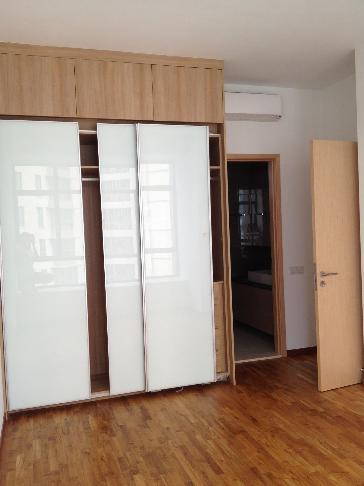 Glorious white glozzy sliding doors built in wardrobe on fake wooden floors in contemporary Wardrobe in master bedroom