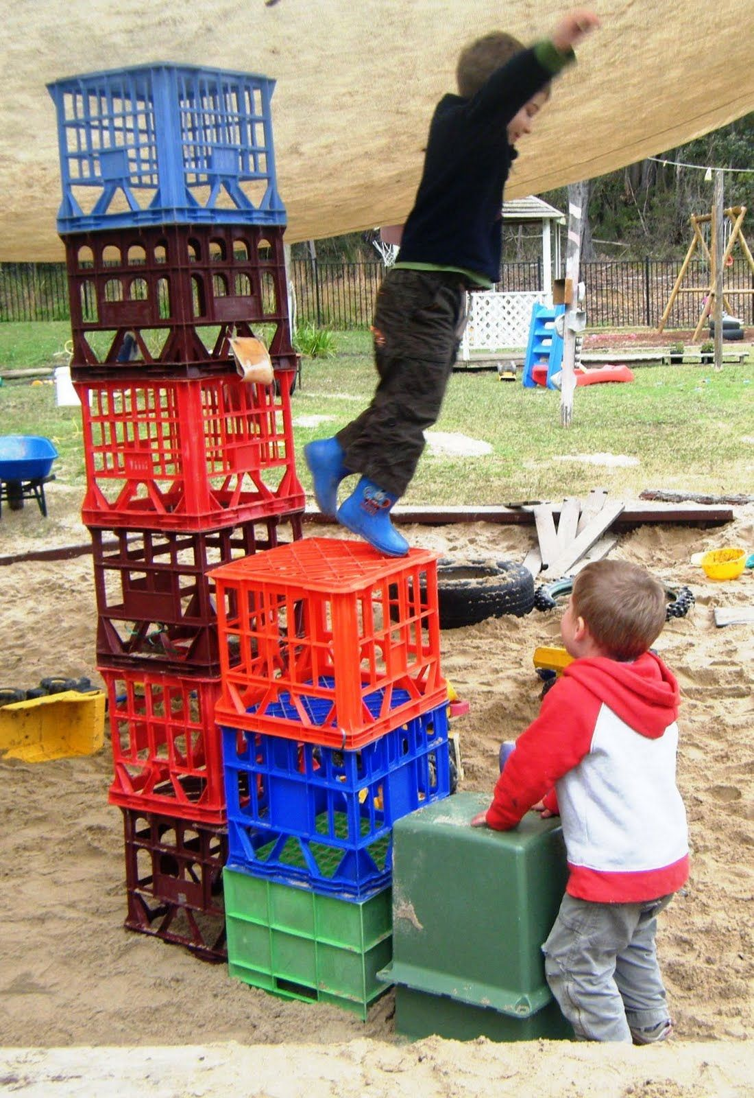 The focus of this photo is the crates for building and construction, as they are light weight, but larger and wider, an item for older kindergarten children.  Supervision would ensure children are not climbing upon them, but allow for imaginative construction and upper body strength and motor skills.