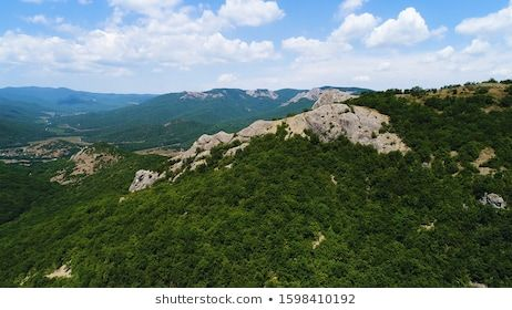 Amazing landscape with mountains covered by green tropical forest on blue sky with clouds on the bakground Shot Aerial view of hilly area with trees and green grass in In...