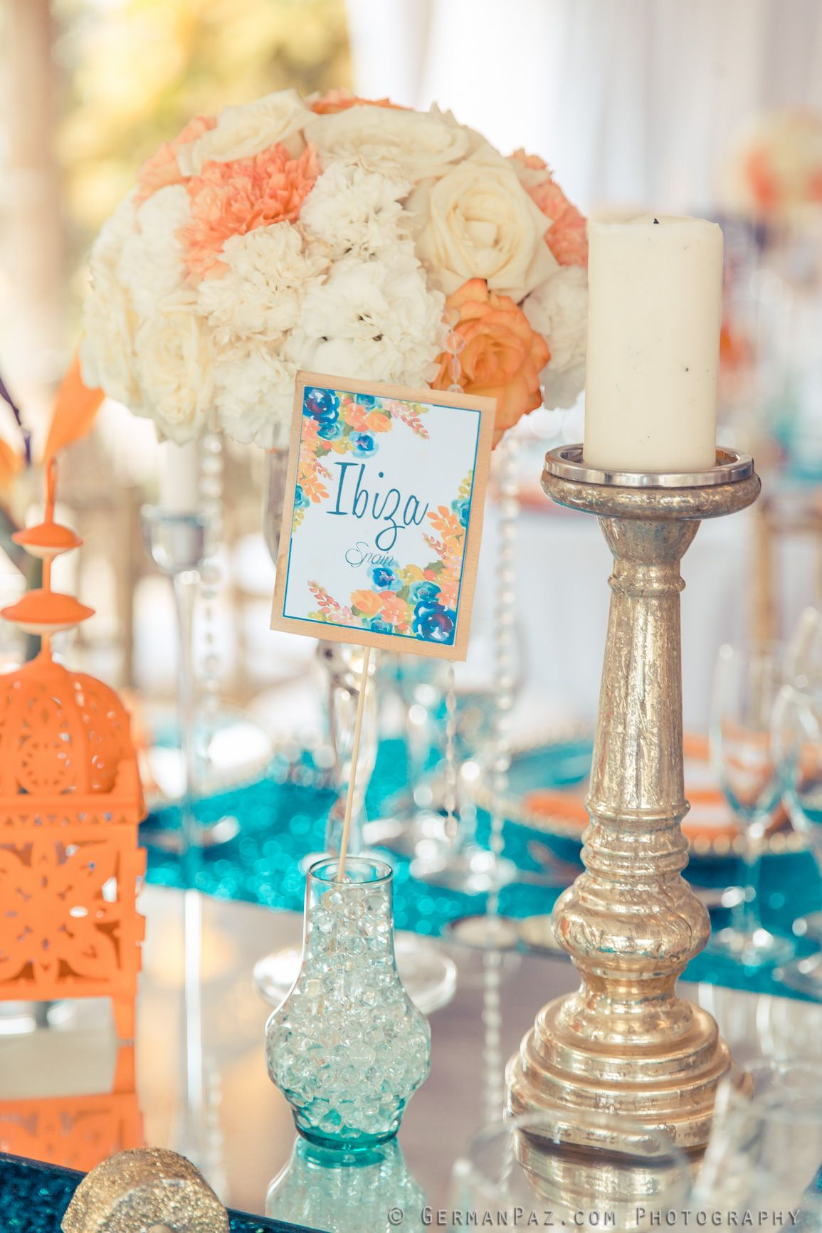 Guest table decor in orange and turquoise with gold accents Venue