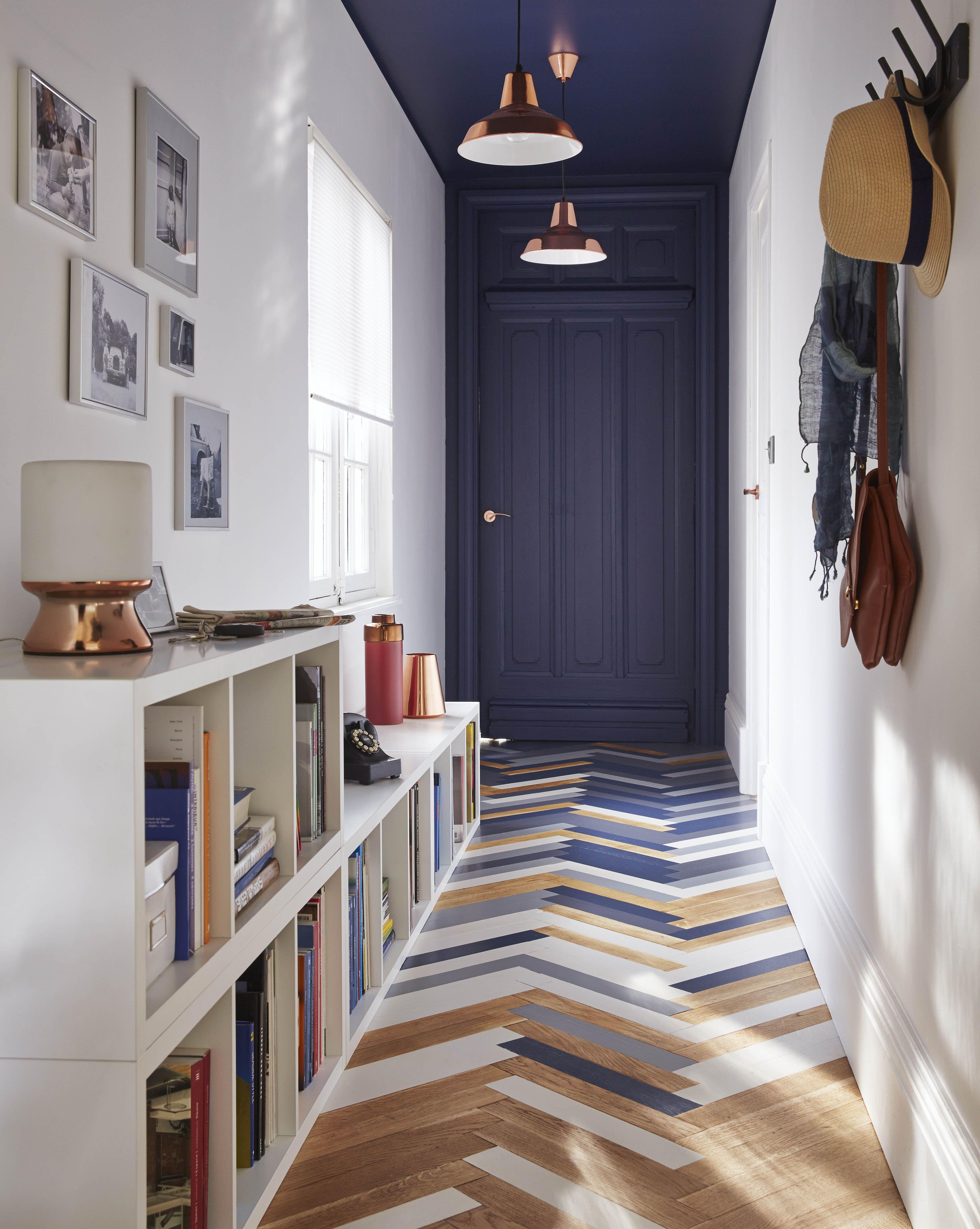 un joli couloir entre avec son parquet peint en tons de bleu ardoise et de blanc le bleu se rpand aussi sur le mur du fond et le plafond