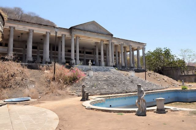 """Statues, pool and the """"Parthenon, Zihuatanejo"""" Mexico. This is an abandoned, never-completed house commissioned by the corrupt and egomaniacal Chief of Police to look like the Parthenon in Athens. More: http://en.wikipedia.org/wiki/Parthenon_Zihuatanejo#Arrest_and_death"""