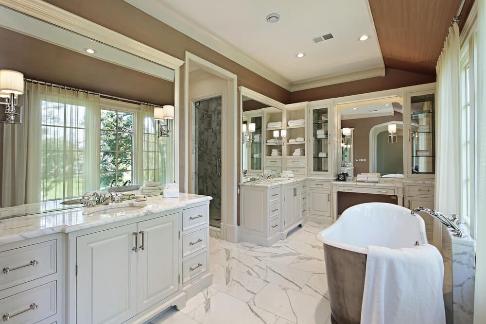 White Tones From Tile Flooring To Painted Wood Cabinetry This Bathroom Features Large Mirrors All Around And A Window Side Pedestal Tub