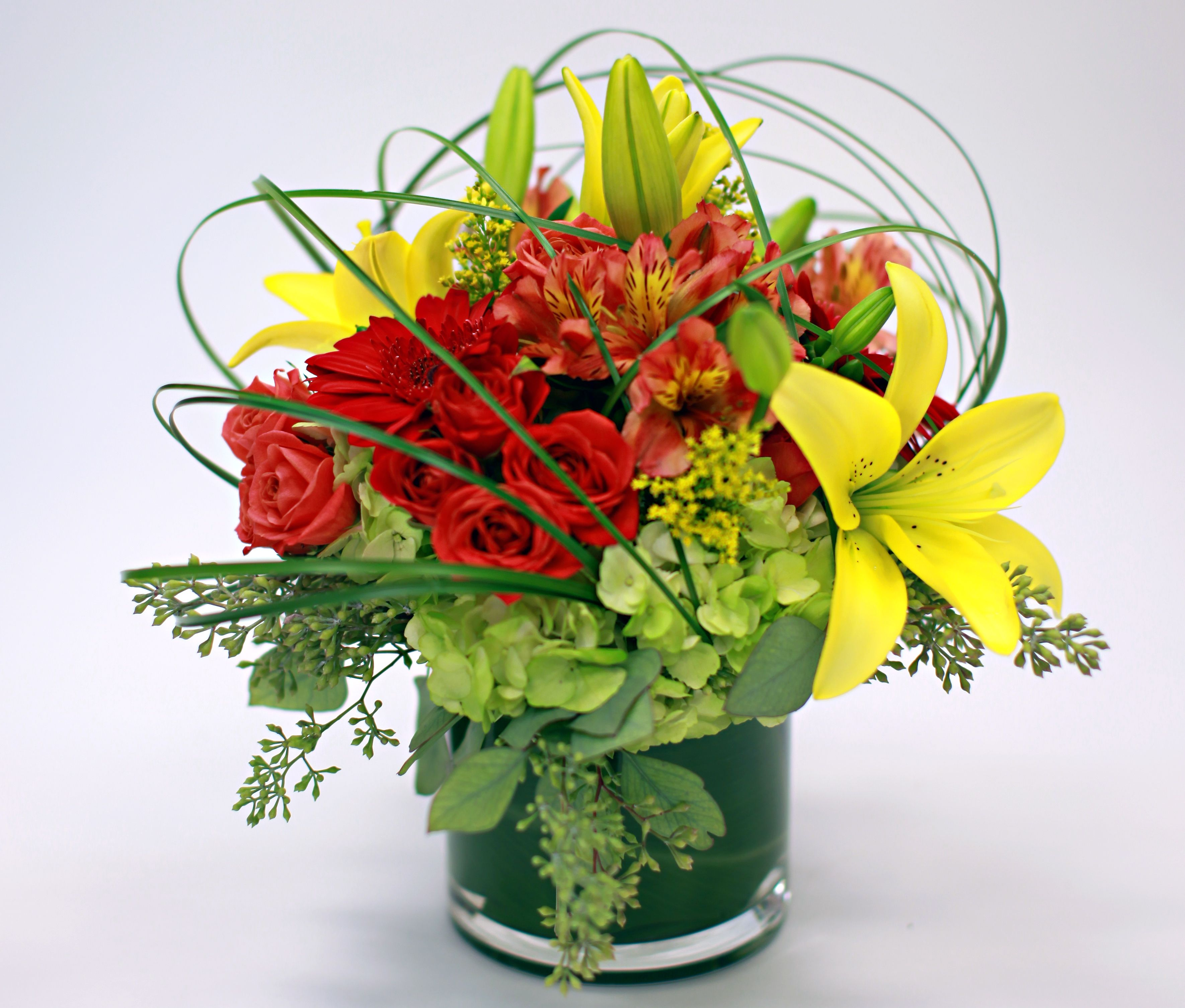 floral arrangement lilies roses bear grass caged