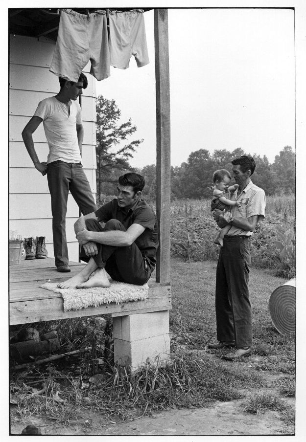 Willie Cornett holding a baby as another on porch looks on and a third looks away.