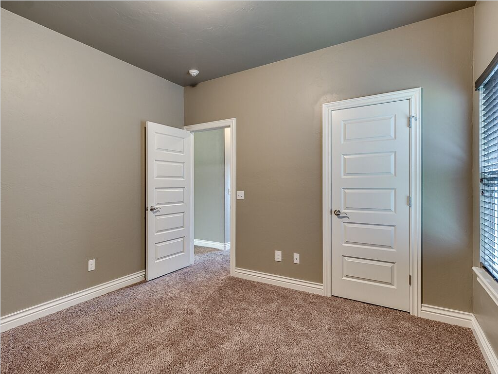 Bedroom completed with earth tones. Tan carpeting, white