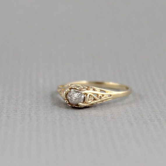 A unique raw, uncut, rough genuine diamond is the highlight on this 14K yellow rose gold solitaire ring. The natural rough diamond is unique - exactly the way it was created by nature. This natural uncut rough diamond is set in a 14K yellow rose gold cast filigree antique style setting. The rough diamond measures approximately 3.5 - 4 mm and weighs approximately 0.50 carat. The width the band is approximately 5.5 mm and tapers to a comfortable 1.5 mm at the bottom of the ring. This ring is…