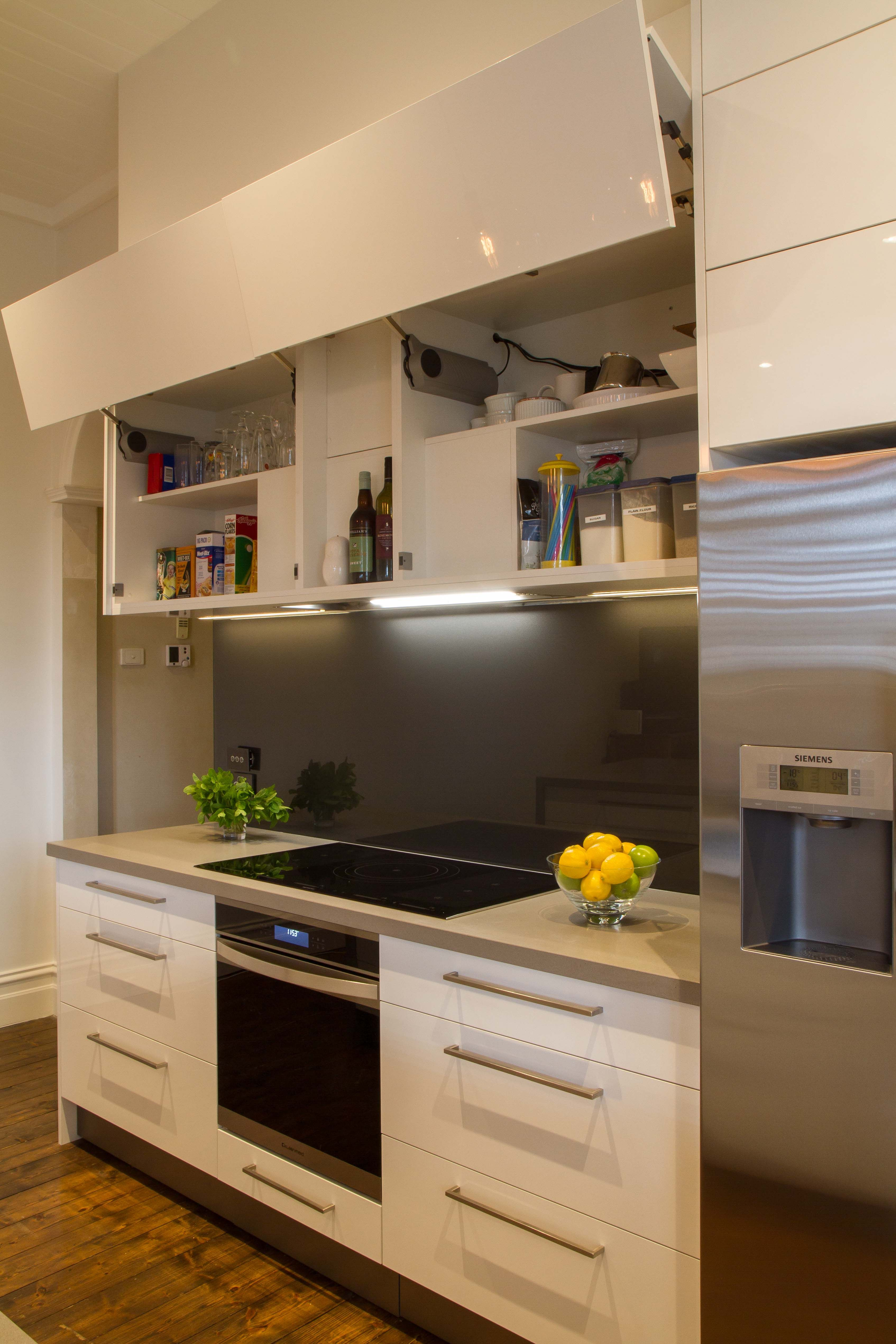 Modern galley style kitchen. Lift up overhead cupboards by