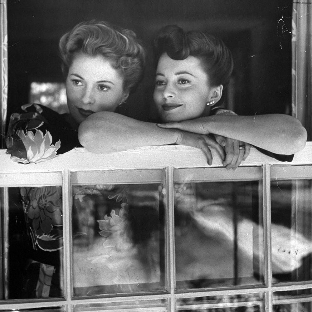 """Sisters Joan Fontaine and Olivia De Havilland - From LIFE 1942: """"As successful movie stars Joan (left) and Olivia make one of their rare appearances together in a window at Joan's home. This year they were winner and runner-up respectively for the Academy Award."""" (Bob LandryThe LIFE Picture Collection/Getty Images) #LIFElegends #siblingday by life"""