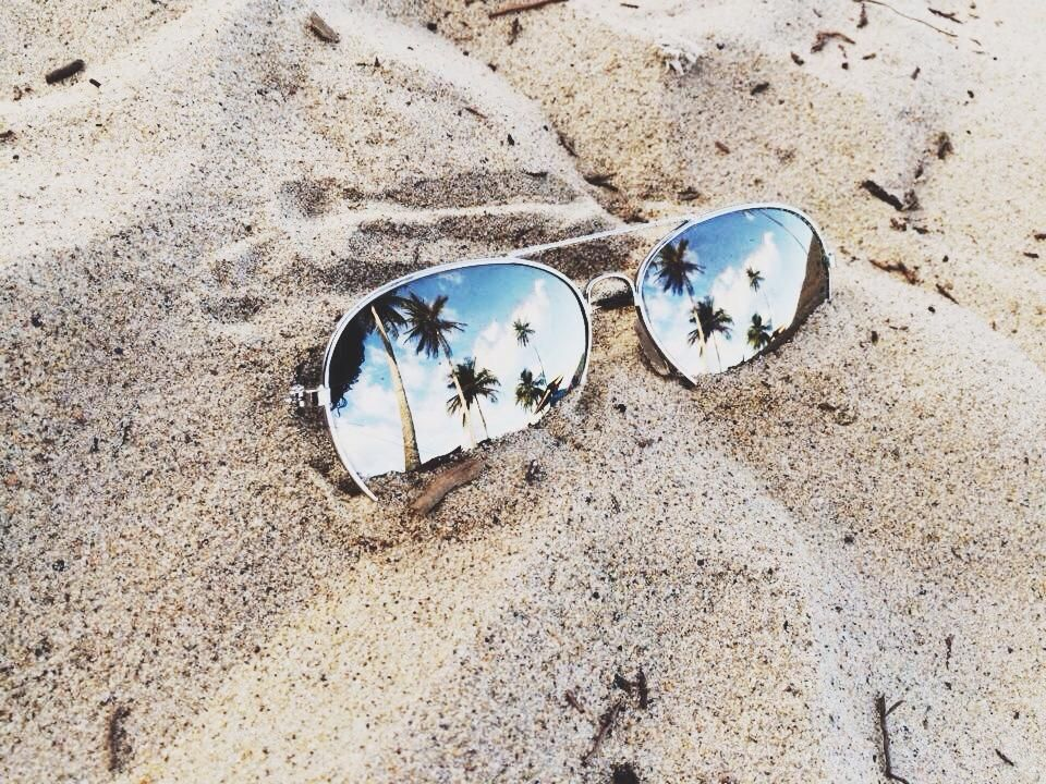 What's cooler than classic aviators half buried in the sand with the iconic #Caribbean coconut trees and blue sky reflected in its lens? Thanks to Rachael Charles for this amazing shot!