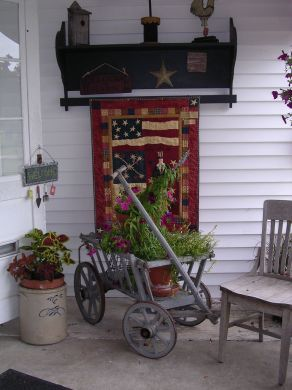 Prim Front Porch...love the old wagon & shelf on the house! I have always wanted an old goat wagon
