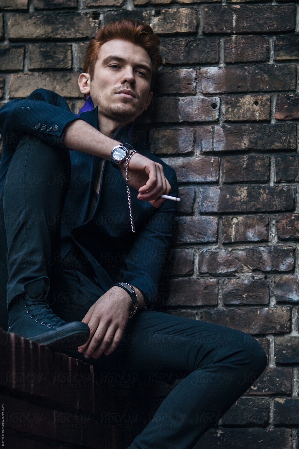 Young Man Leaning Against The Wall Smokes A Cigar Rockabilly Punk Style By Igor Madjinca Stocksy United Male Portrait Punk Fashion Male Poses
